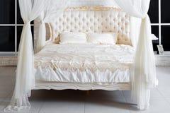Sovrum i mjuka ljusa färger Stor bekväm dubbelsäng för fyra affisch i elegant klassiskt sovrum Lyxig vit med guld- inre D royaltyfri bild
