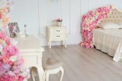 Sovrum i mjuka ljusa färger Stor bekväm dubbelsäng som dekoreras med blommor i elegant klassiskt sovrum arkivbilder