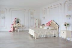 Sovrum i mjuka ljusa färger Stor bekväm dubbelsäng som dekoreras med blommor i elegant klassiskt sovrum royaltyfria bilder