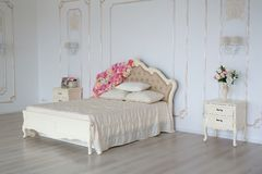 Sovrum i mjuka ljusa färger Stor bekväm dubbelsäng som dekoreras med blommor i elegant klassiskt sovrum arkivbild