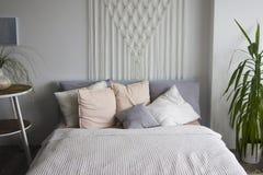 Sovrum i mjuka ljusa f?rger Stor bekv?m dubbels?ng i elegant klassiskt sovrum Vit dubbelsäng med kuddar Sovruminteri arkivbild