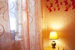 Sovruminterior med gardiner, lampan Arkivbild