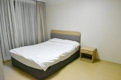 Sovrummet består av en säng, en hylla, ett fönster, en gardin royaltyfria bilder