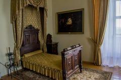 Sovrumruminre med säng, bild, hänger upp gardiner i den forntida gamla slotten royaltyfri fotografi