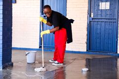 African Woman performing community service volunteer cleaning work at township school