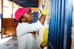 African Women performing community service volunteer cleaning work at township school