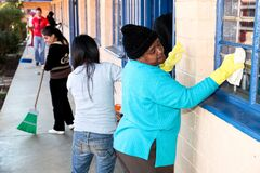 Diverse Women performing community service volunteer cleaning work at township school