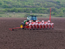 Sowing crops on farmland in the spring. BUCHAREST, ROMANIA - MAY 9, 2015. Sowing crops on farmland in the spring. Spring sowing is suitable for annuals plants Royalty Free Stock Photography