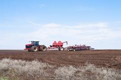 sowing Tractor con la sembradora en el campo Imagen de archivo libre de regalías
