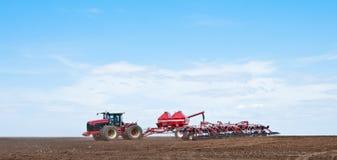 sowing Tractor con la sembradora en el campo Foto de archivo libre de regalías