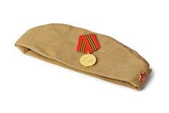 Sowjetische Armeesoldaten Futterkappe und Medaille Stockbild