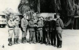 Sowjetische zerstreute Offiziere, welche die Schuhe - die Schuhe der tschechoslowakischen Truppen betrachten prag August 1968 lizenzfreies stockbild