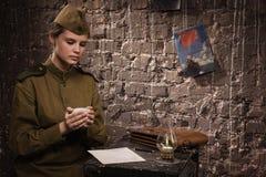 Sowjetischer weiblicher Soldat in der Uniform des Zweiten Weltkrieges liest das lette Lizenzfreie Stockfotografie