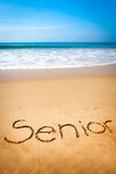 Słowo senior Pisać w piasku, na Tropikalnej plaży Zdjęcia Stock