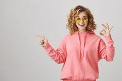 Soy aceptable con ése Tiro del estudio de la muchacha rizado-cabelluda apuesta con la sonrisa brillante que muestra gesto y señal Foto de archivo