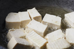 Soy bean tofu while frying in pan Stock Photo