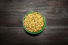 Soy Beans. Yellow soybeans in green ceramic bowl, top view Royalty Free Stock Images