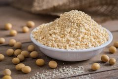 Soy flour in bowl and soybean. Soy flour in a bowl and soybean Royalty Free Stock Images