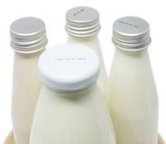 Soy milk bottles on wooden plate isolated Stock Photography