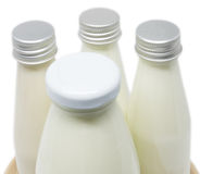 Soy milk bottles on wooden plate isolated Royalty Free Stock Image