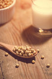Soy milk or soya milk and soy beans in spoon on wooden table. Stock Photo