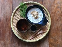 Soy pudding in the black cup topped with  brown sugar and sugar syrup and hot tea on bamboo tray stock images