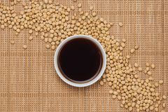 Soy sauce and soy bean on wooden table.  Royalty Free Stock Photo