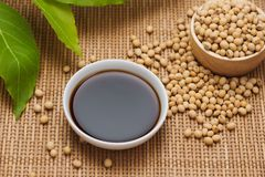 Soy sauce and soy bean on wooden table.  Stock Images