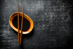 Soy sauce in a bowl with chopsticks. On dark rustic background royalty free stock image