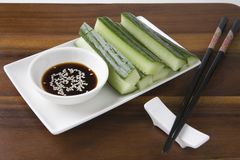 Soy Sauce With Cucumber Slices And Chopsticks On Table Royalty Free Stock Photography