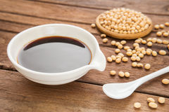 Soy sauce and soy bean on wooden background Royalty Free Stock Photography