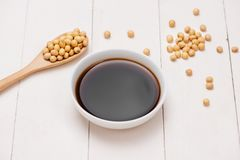 Soy sauce and soy bean on wooden table.  Royalty Free Stock Photography