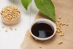 Soy sauce and soy bean on wooden table.  Royalty Free Stock Images