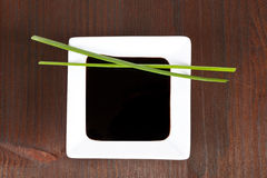Soy sauce for sushi. Soy sauce in white square bowl in dark wooden background with chive. Sushi concept Stock Photo