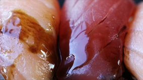 Soy Sauce on Sushi. Drizzling soy sauce on salmon and tuna sushi stock video footage