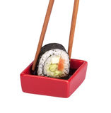 Soy sauce with sushi roll and chopsticks. Isolated royalty free stock image