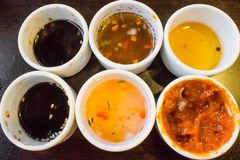 Soy sauce, vinegar, balsamic oil and chili paste on white small saucer lined in a row stock photo