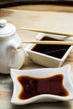 Soy sauce in a white dish and chopsticks Stock Image