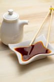 Soy sauce in a white dish and chopsticks Stock Photos