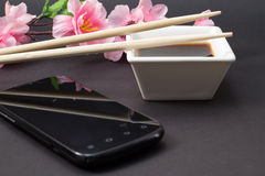 Soy sauce in a white dish and chopsticks Royalty Free Stock Images