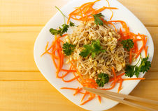 Soy sprouts salad with carrots and parsley. On white plate on wooden desk Stock Photography