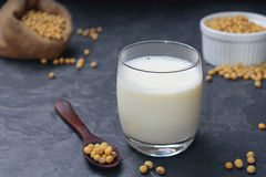 Soya bean milk. In clear glass with beans on wooden spoon and sackcloth bag royalty free stock image