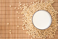 Soya milk. Glass of soya milk viewed from top surrounded by soya beans Stock Images