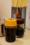 Soya, vinäger, chiliolja, socker och pinnar på en tabell av ett Hong Kong utformar den traditionella kantin Royaltyfri Foto
