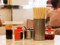 Soya, vinäger, chiliolja, socker och pinnar på en tabell av ett Hong Kong utformar den traditionella kantin Royaltyfria Bilder