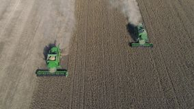 Soybean field, aerial view on green combines working on the large agricultural territory during of harvest