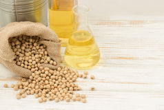 Soybean in hemp sack bag  with oil in laboratory glass setup on wooden table. Stock Photo