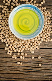 Soybean oil in ceramic bowl with soybean seed on wooden backgrou. Soybean useful vitamins and health benefits Royalty Free Stock Images