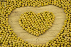 With the soybean is placed into the heart. The kitchen chopping board, soy is placed into the heart Royalty Free Stock Photo