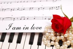 Soyeux rouge s'est levé avec les notes musicales Photos stock